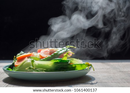The steaming hot  from Mixed vegetables on white bowl dark background selective focus. #1061400137