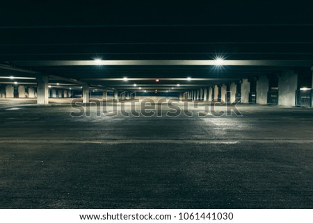 Grungy, dimly lit empty parking garage with overhead lights and an exit sign hanging from the ceiling. #1061441030