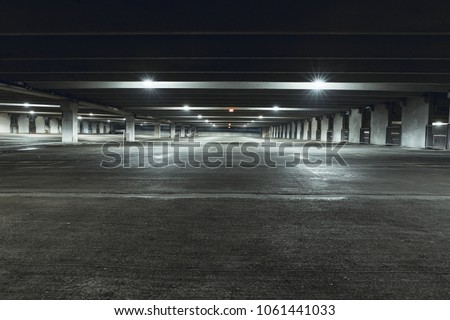 Grungy, dimly lit empty parking garage with overhead lights and an exit sign hanging from the ceiling. #1061441033
