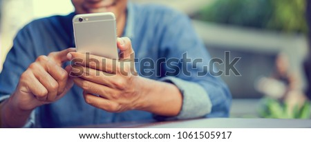 Close up asian man using smart phone mobile device for play or shopping online or check time and date , teenager with technology and social distance concept Royalty-Free Stock Photo #1061505917