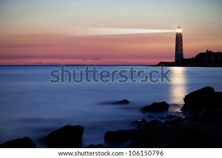Seascape at sunset. Lighthouse on the coast Royalty-Free Stock Photo #106150796