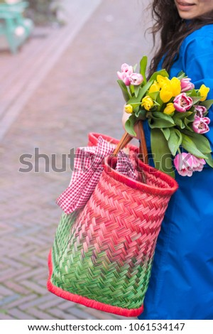 A girl in a blue raincoat. In his hands a basket for shopping and a bouquet of flowers. yellow and pink tambourines. #1061534147