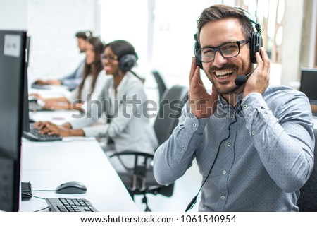 Portrait of cheerful customer support telephone operator in call centre #1061540954