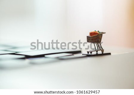 Close up of shopping cart or trolley miniature figure toy on laptop computer. Shopping, retail and e-commerce concept. #1061629457