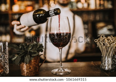 Bartender pouring red wine from a bottle in a wine glass, selective point of view on a wine glass #1061669315