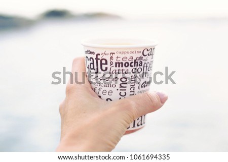 A female hand is holding a cup of coffee in front of sea and beautiful view  #1061694335