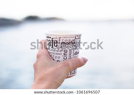 A female hand is holding a cup of coffee drinking in front of blue sea in the morning on the way to work and enjoying beautiful view ,blurred background #1061696507