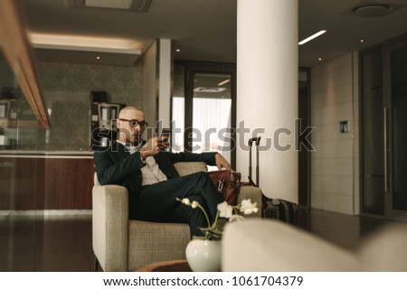 Business traveler waiting in airport lounge and using mobile phone. Businessman waiting for fight at airport lounge. #1061704379