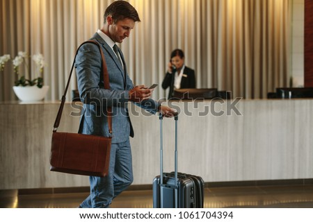Young businessman walking in hotel lobby and using mobile phone. Business traveler arriving at his hotel. #1061704394