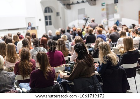 Female speaker giving presentation in lecture hall at university workshop. Audience in conference hall. Rear view of unrecognized participant in audience taking notes. #1061719172