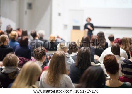 Female speaker giving presentation in lecture hall at university workshop. Audience in conference hall. Rear view of unrecognized participant in audience. Scientific conference event. #1061719178