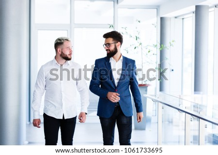 Young Business Colleagues Discussing While Walking  #1061733695