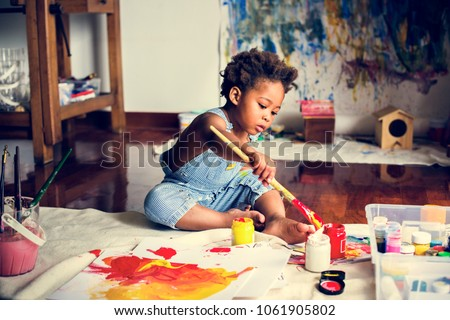 Black kid enjoying his painting Royalty-Free Stock Photo #1061905802