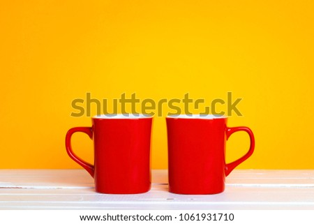 Two red coffee mugs on a yellow background with copt space. Tea or coffee time.  #1061931710