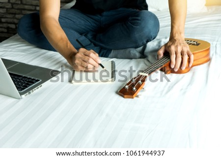 young man write a song or music with her Ukulele play #1061944937