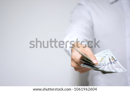 Businessman holding dollar money and giving money to you with copy space. Banker with money in hand displaying cash for customer loan, money transfer, investment and success concept. Selective focus. #1061962604