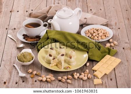 Pistachio truffles on green dish.  #1061963831