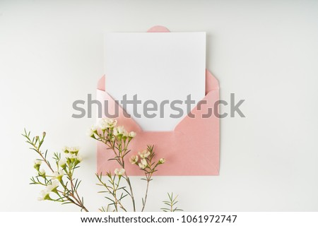 Minimal composition with a pink envelope, white blank card and a wax flower on a white background. Mockup with envelope and blank card. Flat lay. Top view. Royalty-Free Stock Photo #1061972747