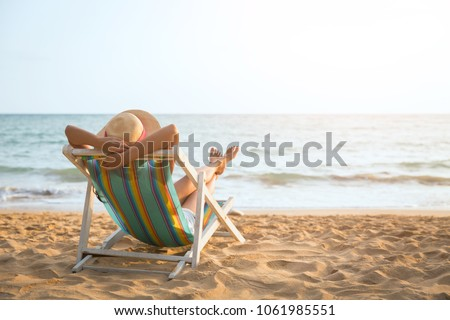 Summer beach vacation concept, Asia woman with hat relaxing and arm up on chair beach at Koh Mak, Trad, Thailand Royalty-Free Stock Photo #1061985551