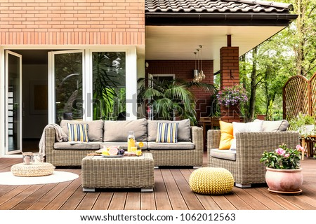 Yellow pouf next to a rattan armchair and flowers on wooden patio with striped pillows on sofa #1062012563