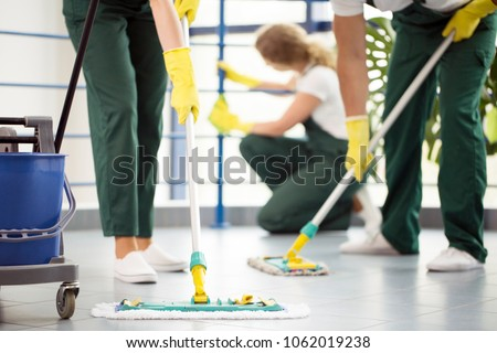 Coworkers moping the floor and a woman dusting a railing in an office #1062019238