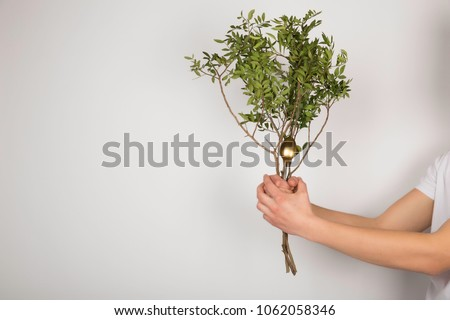A guy holding a tree branch with a spoon on a white background. #1062058346