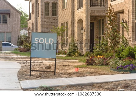 Close-up front porch of newly built detached single-family home with sold out sign. Brand new properties in new-established community, construction zone with unfinished landscape Irving, Texas, USA