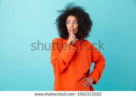 Image of african woman 20s in casual clothing holding index finger on lips and asking to keep silence isolated over blue background
