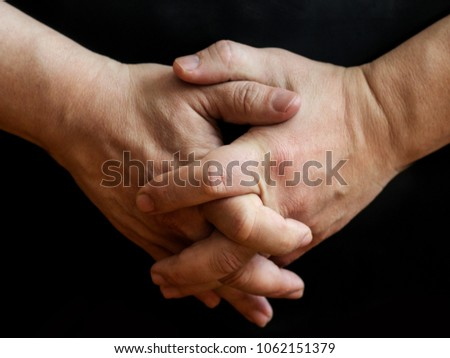 Two compressed male hands on a black background #1062151379