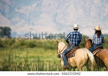 a couple horseback riding from behind overlooking wide open field and mountains of Utah wilderness