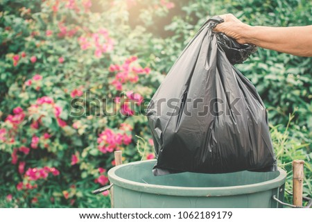 Old hand holding plastic bag in to trash  #1062189179