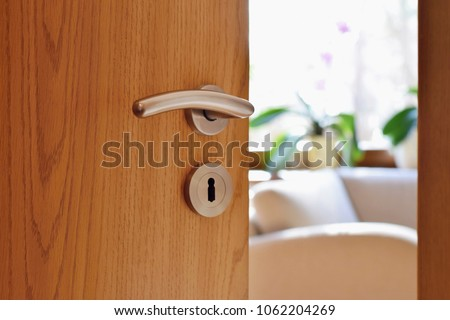 Half opened door into the cozy home interior Royalty-Free Stock Photo #1062204269