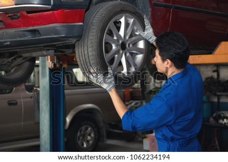 Asian mechanic checking wheel under the car to repair, japanese mechanic portrait style, mechanic maintenance working under car #1062234194
