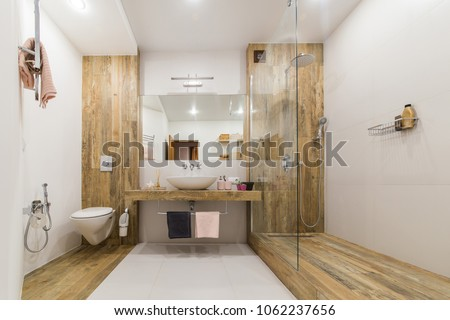 Modern bathroom interior combined with toilet. Shower room and toilet are covered with tiles in the color of wood, white walls and a white floor and a washbasin with a large mirror in the center #1062237656