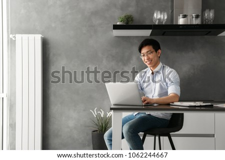 Portrait of a happy young asian man working on laptop computer while sitting at the table with paperwork at home #1062244667