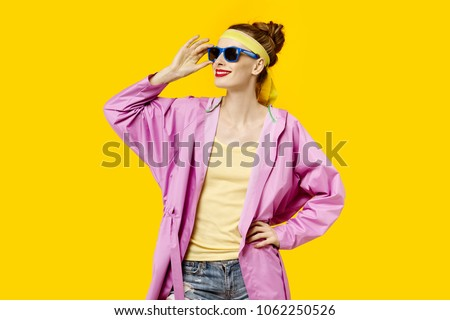 Young woman on a yellow background and pink coat and sunglasses. Colour obsession concept.  Minimalistic style. Stylish Trendy #1062250526