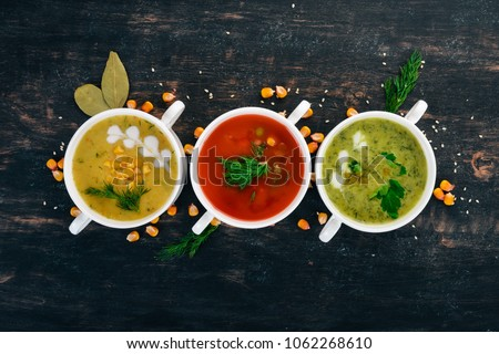 Set of hot, colored vegetable soups. Broccoli soup, corn, tomato soup. Healthy food. On a black wooden background. Copy space. #1062268610