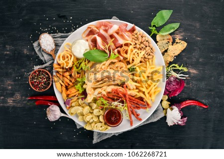 A selection of snacks for beer. Chips, sausage, cheese. Top view. On a wooden background. Copy space. #1062268721