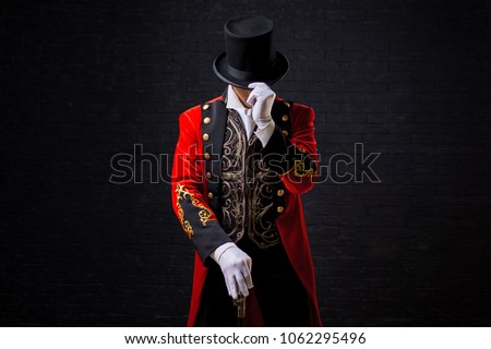Showman. Young male entertainer, presenter or actor on stage. The guy in the red camisole and the cylinder. Looking down, hand on the hat