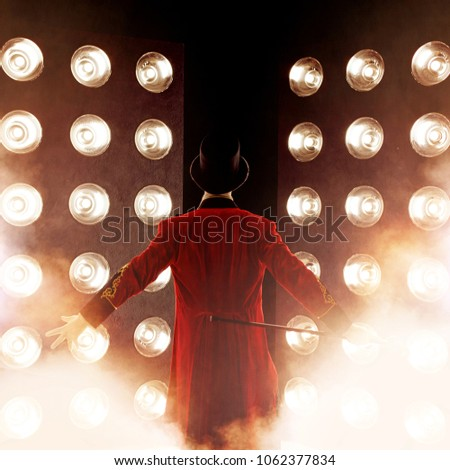 Showman. Young male entertainer, presenter or actor on stage. Back, arms to sides, smoke on background of spotlight Royalty-Free Stock Photo #1062377834