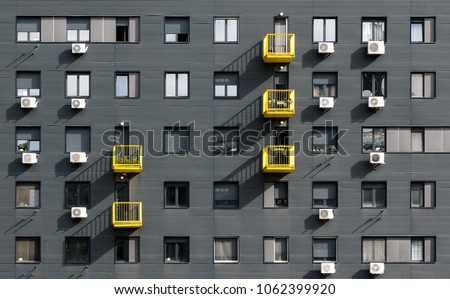 A view at a straight facade of a modern building with a dark grey facade and yellow balconies in Belgrade, Serbia #1062399920