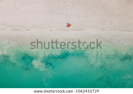 Drone photo. The couple lies on the beach #1062410729