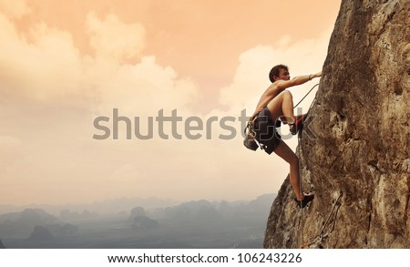 Young man climbing on a limestone wall with wide valley on the background Royalty-Free Stock Photo #106243226