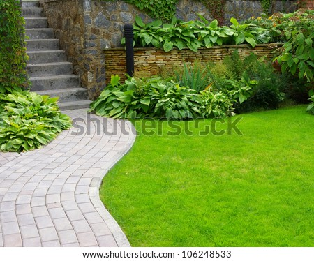 Garden stone path with grass growing up between the stones #106248533