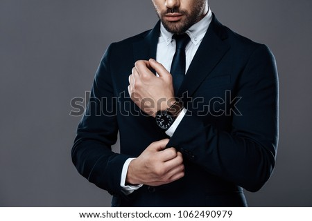 Close-up handsome and successful man in an expensive suit. He is in a white shirt with a tie. A strong, stylish successful man in a suit posing. Royalty-Free Stock Photo #1062490979