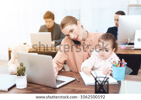 The woman with the child came to work. She works with her daughter in her arms. This is a business office. #1062500192