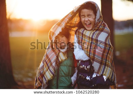 Sister and brother wrapped in a blanket trying to stay warm on a cold day outdoors #1062520280