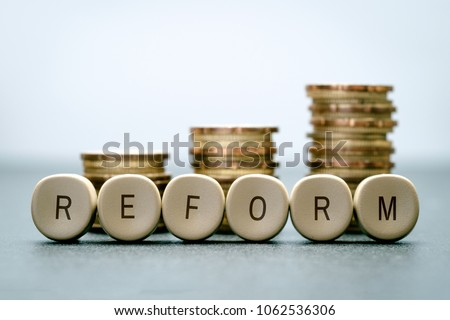The word REFORM on letter blocks and stand coins, Tax Reform concept. #1062536306
