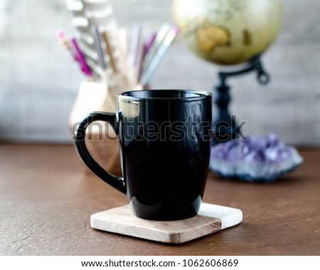 black mug mockup with globe and pens on leather #1062606869