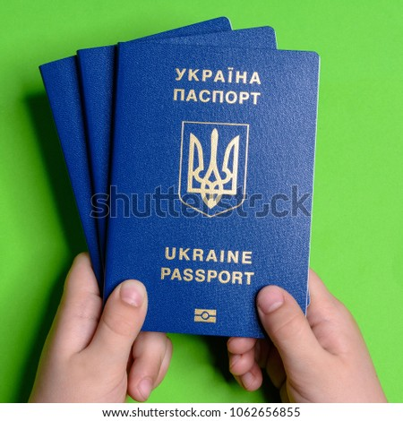 The hand of a teenager holds the Ukrainian biometric passport green background #1062656855